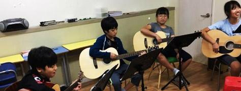 기타를 연주하고 있는 금샘지역아동센터 아이들