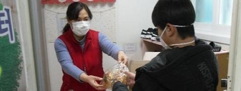 대구 멘토지역아동센터에서 식료품을 나눠주는 선생님과 아이 모습